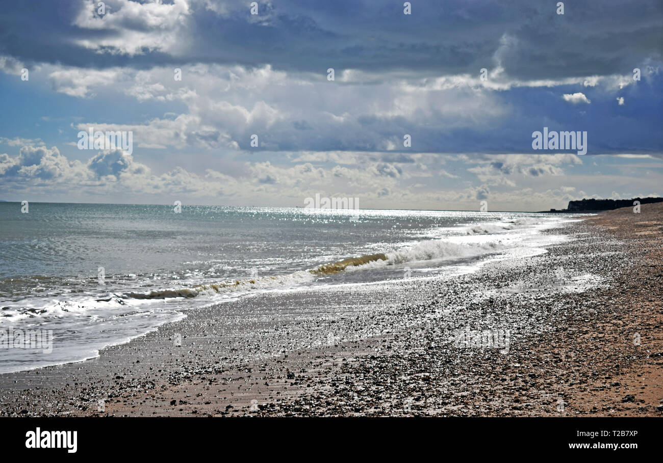 Beautiful sea view of the rough waves breaking onto the pebble beach with a dramatic cloudy sky along the Kent coastline - Stock Image