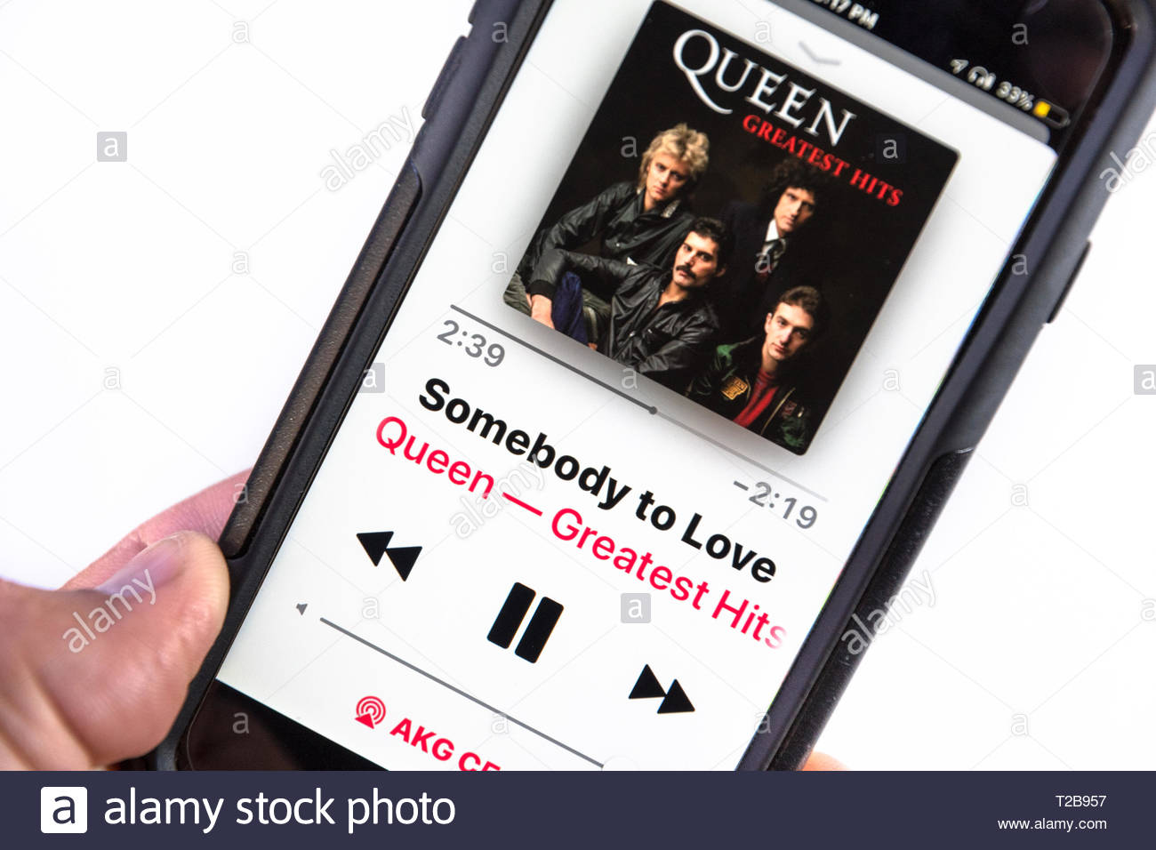 Listening Queen music on a smartphone. The screen shows 'Somebody to Love' and the cover of the album 'Greatest Hits' - Stock Image