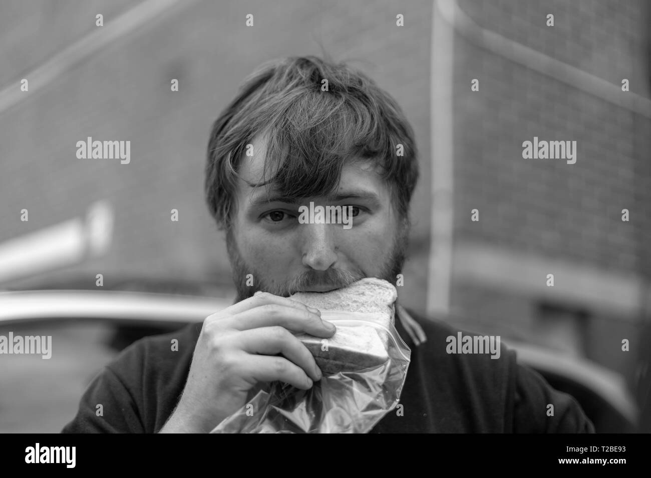 A tradesman with a dirty face eats his lunch in Melbourne - Stock Image