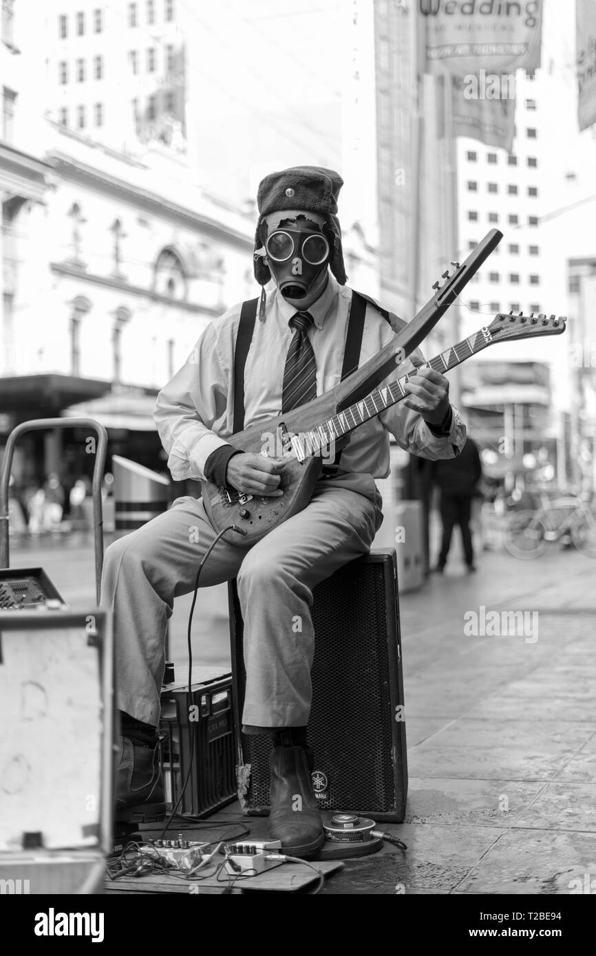 Street busker playing a guitar with a gas mask on. - Stock Image