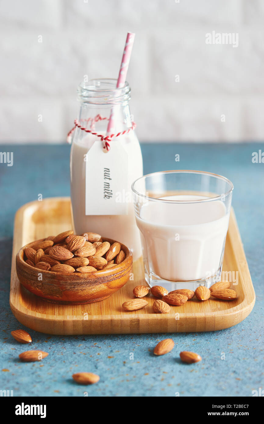 Vegan substitute dairy milk. Glass with non-dairy milk and ingredients. - Stock Image