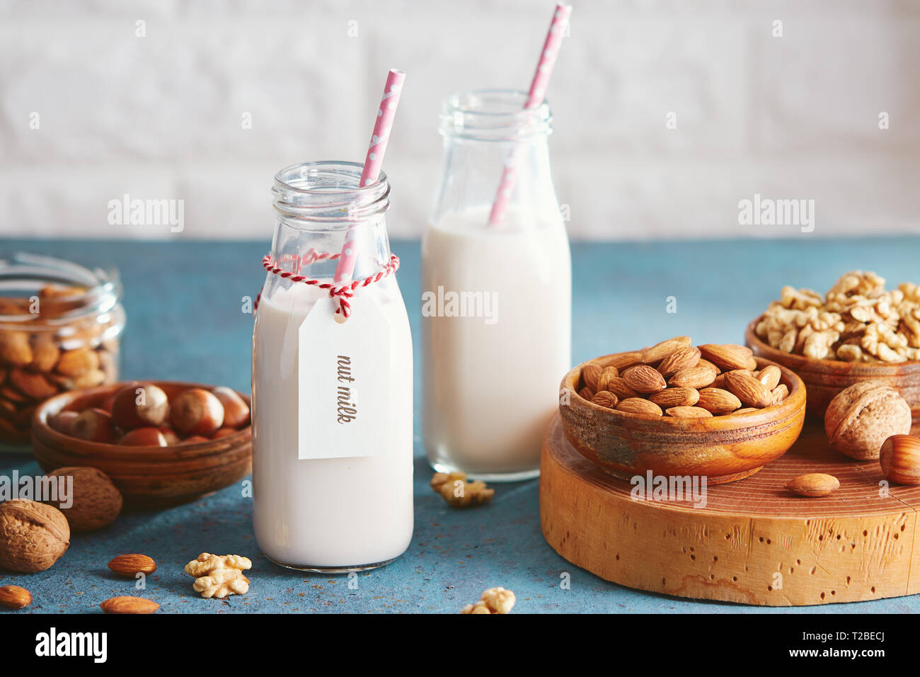 Vegan substitute dairy milk. Glass bottles with non-dairy milk and ingredients. - Stock Image