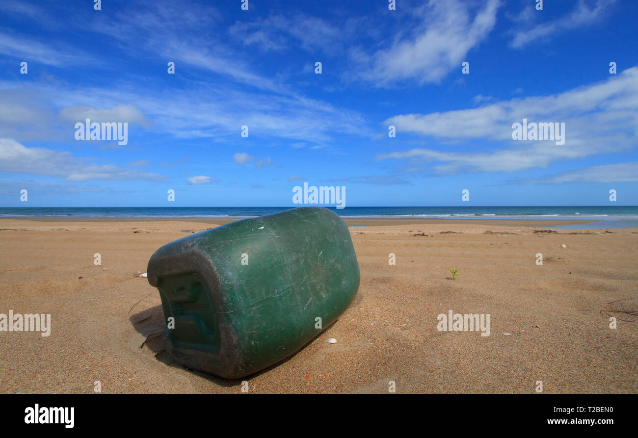A green plastic container washed up on a pristine beach on the west coast of Cape York, Australia.   The container has likely been discarded from a fi - Stock Image