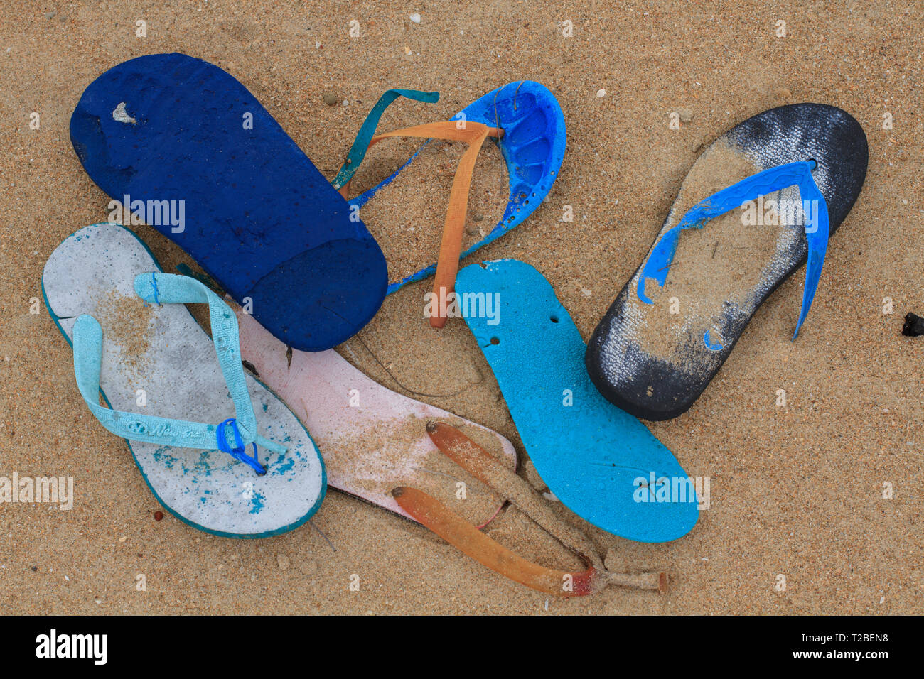 Plastic Flip flops collected on a beach on the West coast of Cape York Australia background.   Flip flops or thongs have washed off fishing vessels op - Stock Image