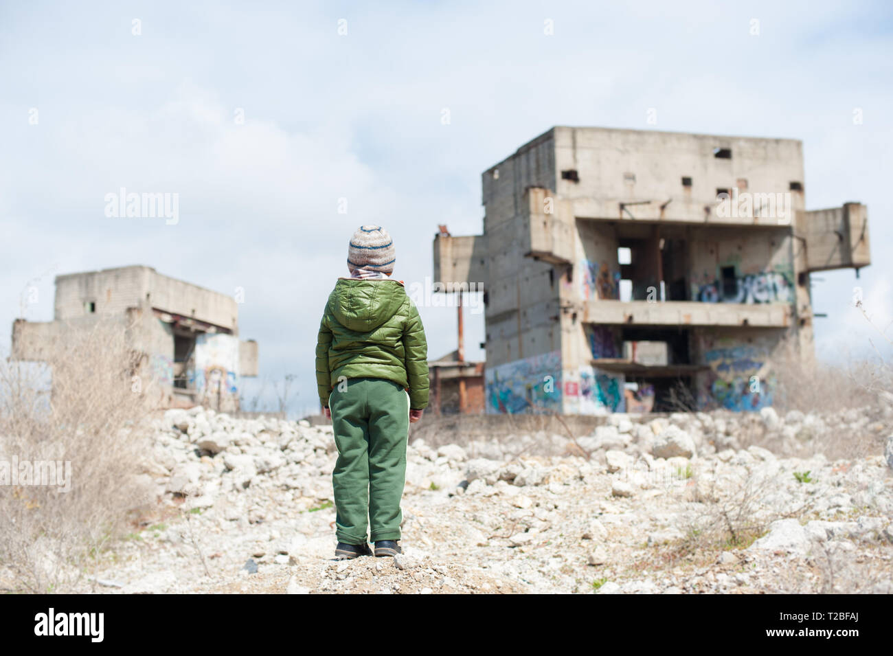 one little child in green jacket standing on ruins of destroyed buildings in war zone - Stock Image