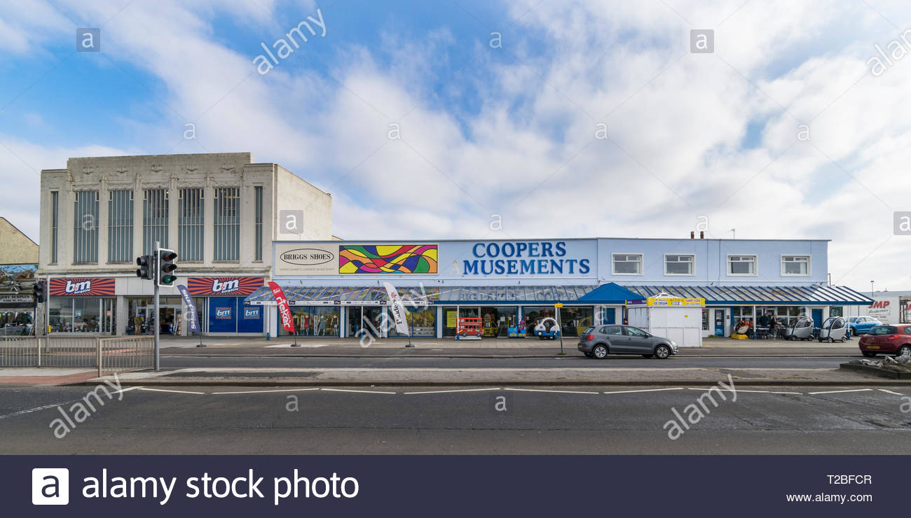 Art deco building (left) on Marine Drive, Morecambe, previously occupied by Woolworths, with Coopers Amusements and shops on the right. - Stock Image