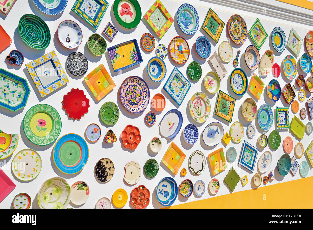 Dozens of colorful ceramic plates contrasting with a white painted outdoor wall on a sunny day - Stock Image