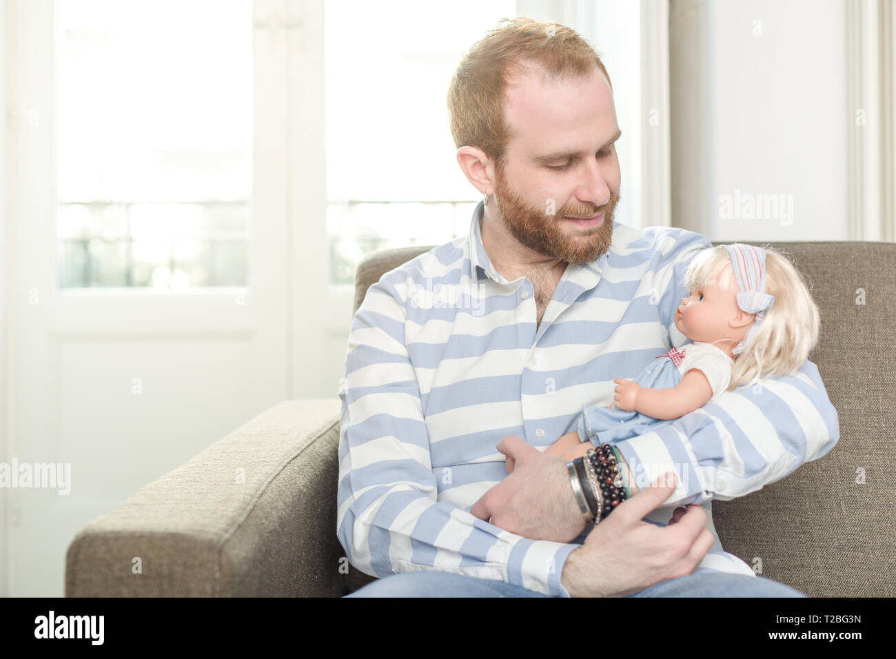 Smiling Man Sitting on a Couch Cradling a Doll - Stock Image