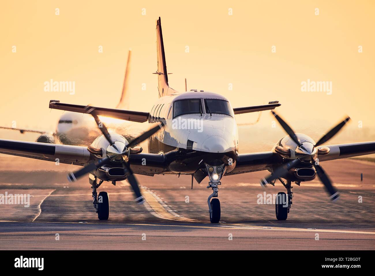 Modern propeller plane against commercial airplane on runway. Traffic at airport during sunset. - Stock Image