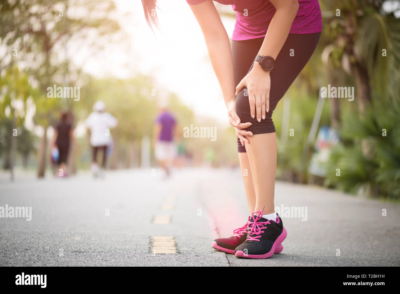 Runner sport knee injury. Woman in knee pain while running work out in park. Health care concept. - Stock Image