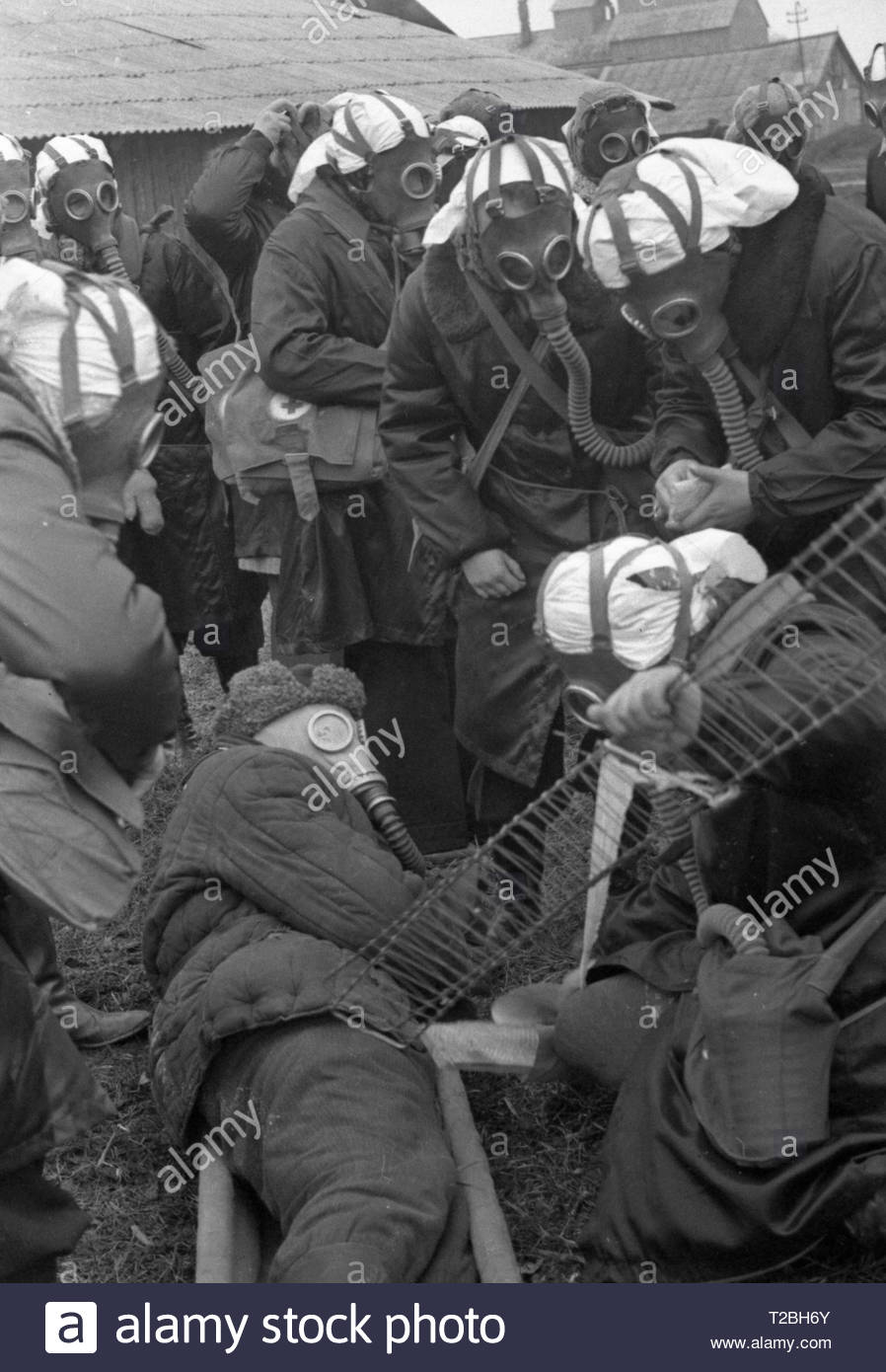 Civil defense exercises. In Soviet times our society was regularly preparing for a chemical attack from the side of capitalist countries. On the photo simulates the situation when chemical attack still occurred. Female nurses in gas masks. They put on a stretcher the alleged victim who is also in a gas mask. Women provide him with first aid. Stock Photo