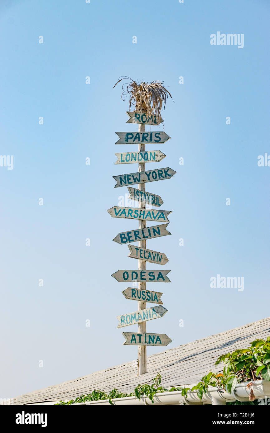 Nessebar, Bulgaria - 7 Sep 2018: Direction signs to different cities in the world on top of a roof in Nesebar ancient city. Nessebar or Nesebr is a UN - Stock Image