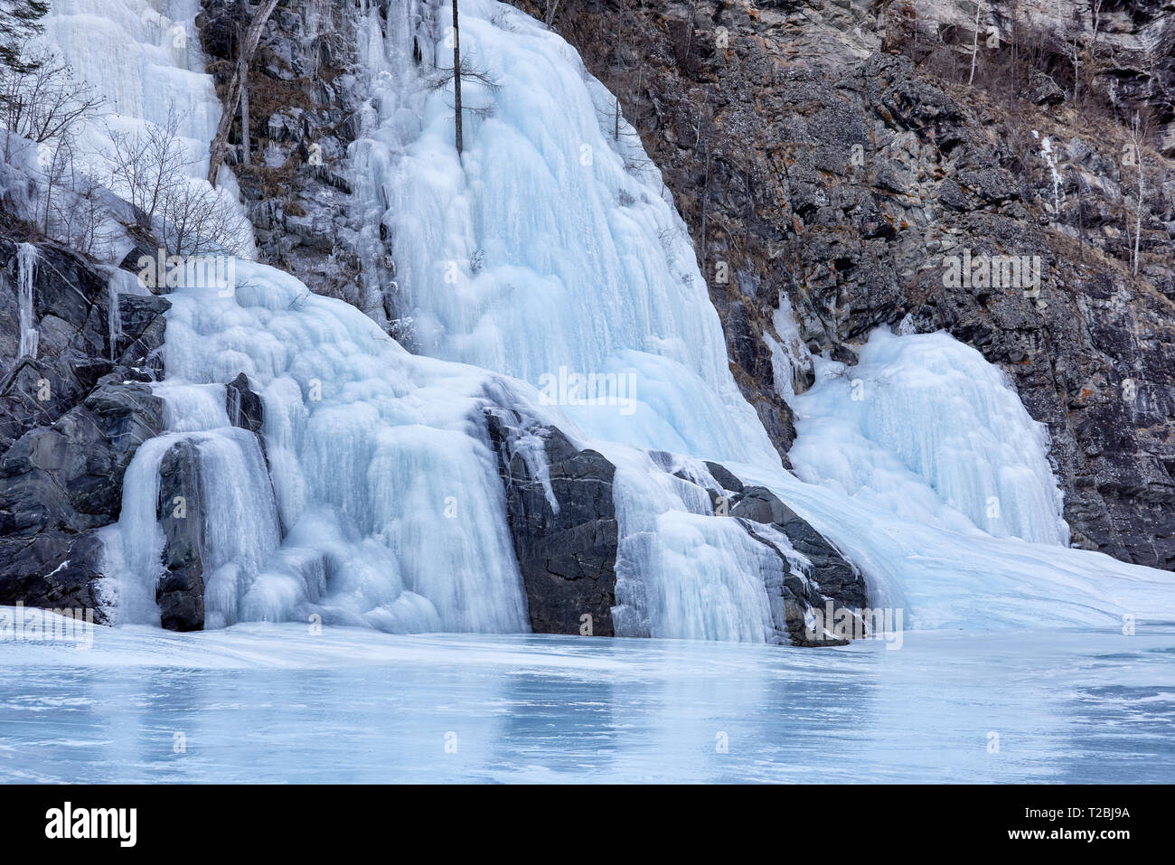 Fairy icefall is result of freezing of small falling streams at negative ambient temperatures. Formation of bizarre forms of frozen spring water - Stock Image
