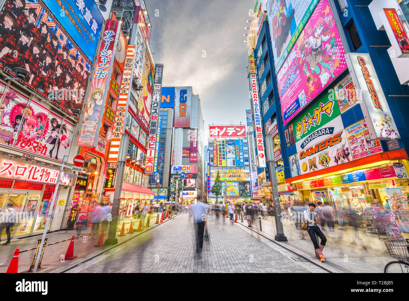 TOKYO, JAPAN - AUGUST 1, 2015: Crowds pass below colorful signs in Akihabara. The historic electronics district has evolved into a shopping area for v - Stock Image