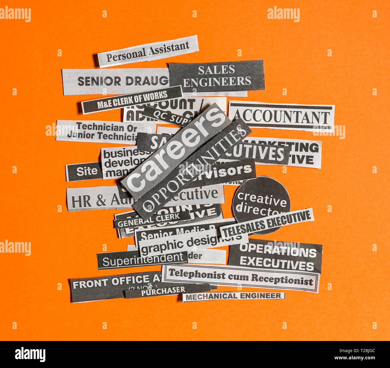Jobs or careers concept: multiple job titles or occupations cut off from newspaper with Careers opportunities on top of the pile and on orange backgro - Stock Image