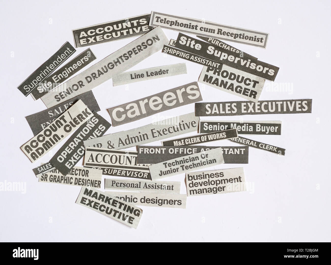 Jobs or careers concept: job titles or occupations cut off from newspaper and with Careers at the centre of the pile - Stock Image