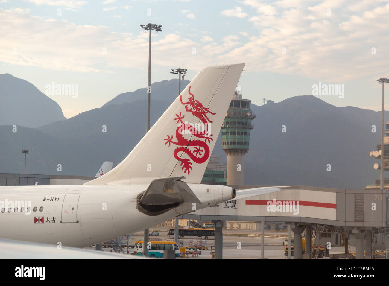 Cathay Dragon (Dragon Air's) docked in the airport with air traffic control tower in the background - Stock Image