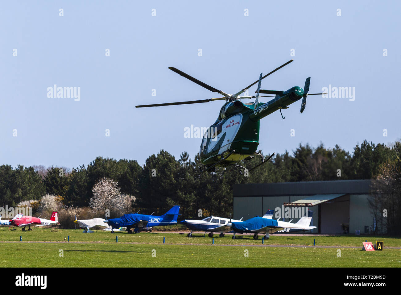 Helicopter Operating for Essex & Herts Air Ambulance Taking off from Earls Colne Aerodrome in Essex on a Fine Spring Day - Stock Image