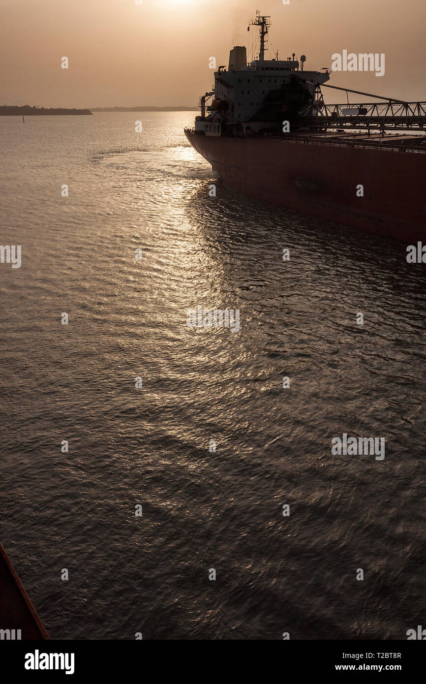 Port operations for managing and transporting iron ore. Sunrise across deck and holds of iron ore transhipment vessel while docking and before loading - Stock Image