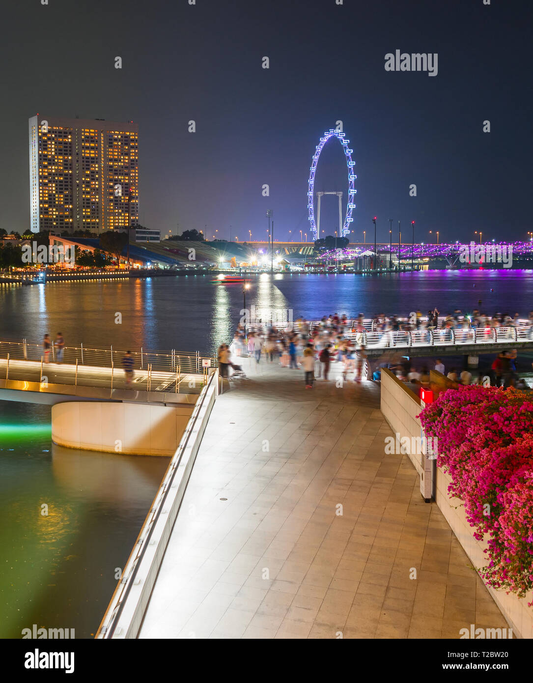 Tourists walking by Singapore embankment, illuminated Flyer, city skyline with modern architecture in background - Stock Image