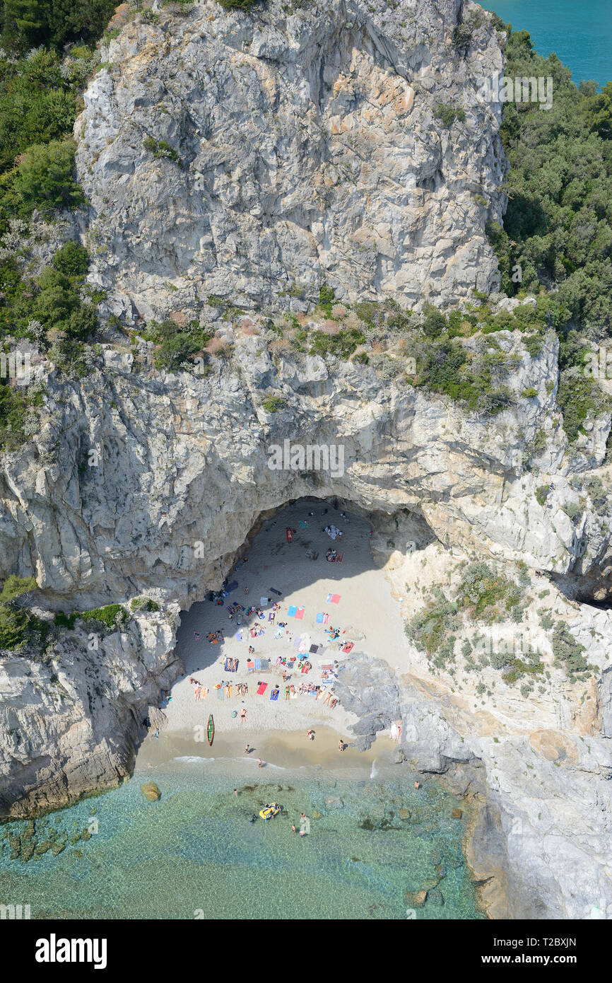 SEASIDE CLIFF WITH A LARGE CAVE AT ITS FOOT OFFERING SHADE TO TOURISTS (aerial view). Varigotti, Liguria, Italy. - Stock Image