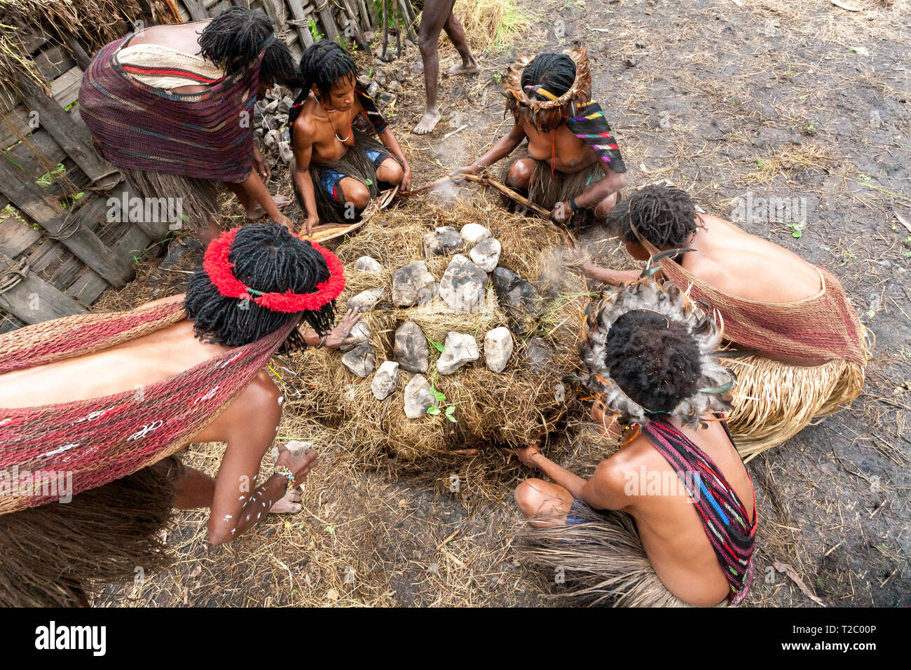 Wamena, Indonesia - January 9, 2010: Dani women cooking food into a hole filled with hot stones. Baliem Valley, Papua New Guinea. - Stock Image