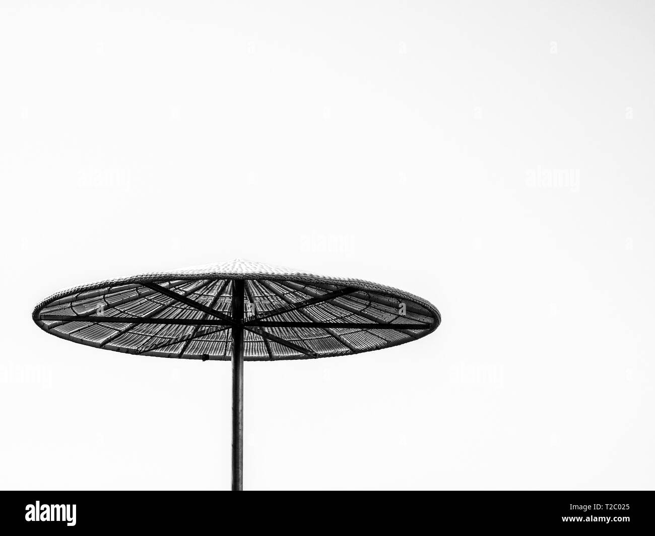 Black and white straw awning in sunny summer day, tropical background. - Stock Image