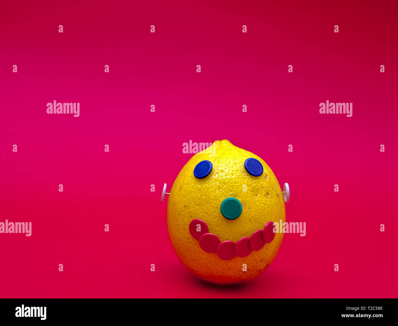 A happy face made with a lemon and colorful pins. Isolated on magenta background. - Stock Image
