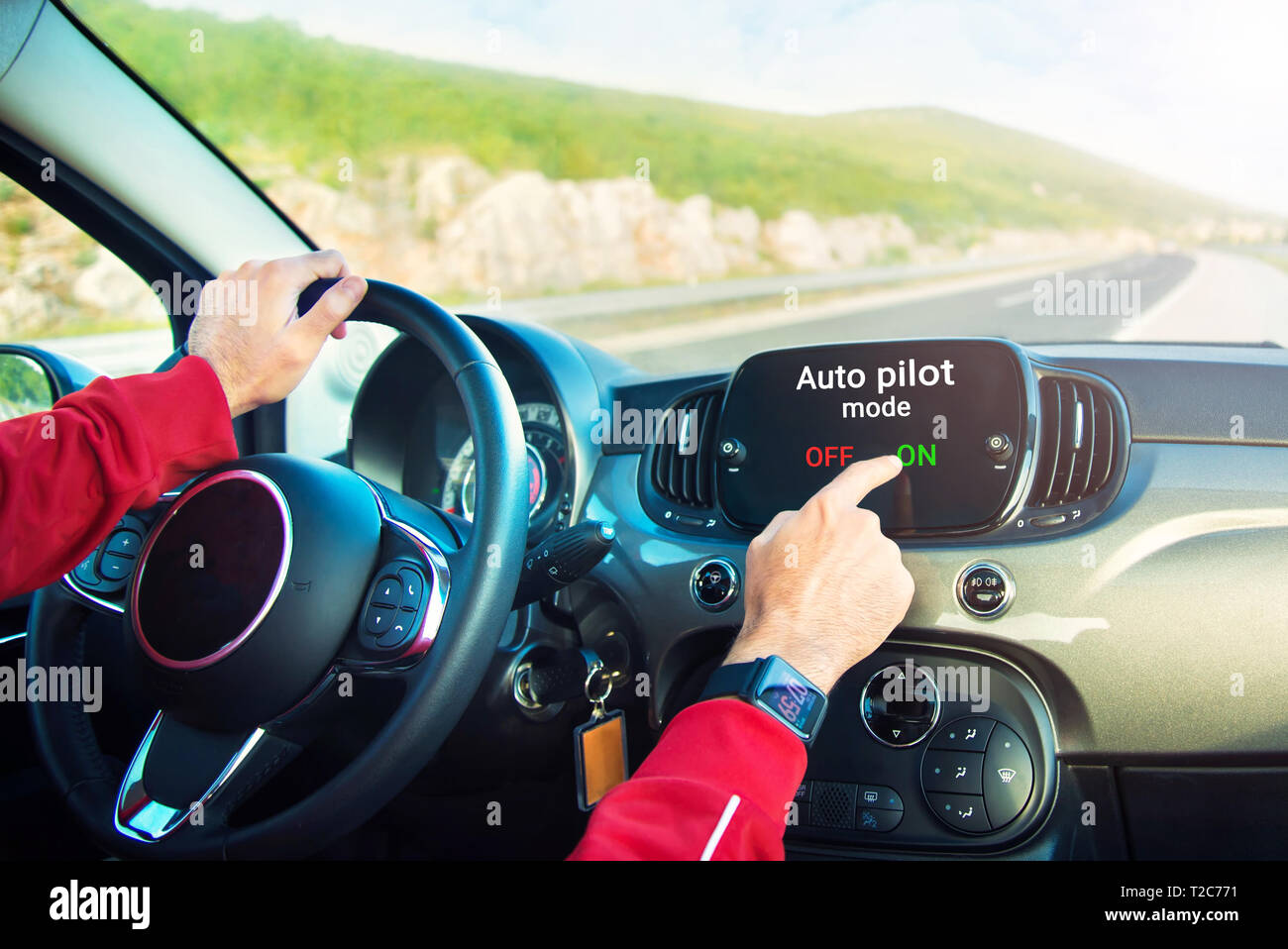 male hands with smart watch on switching on auto pilot mode on car display on highway - Stock Image