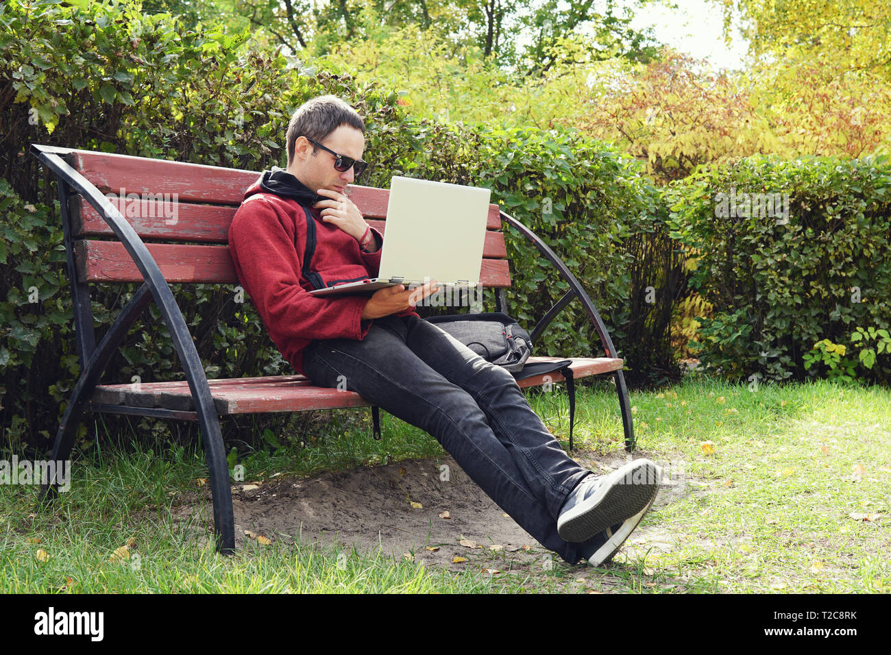 Young stylish male student texting message on laptop in park on autumn. The guy works at a laptop in the open air. Remote work. Thoughtful young man l Stock Photo