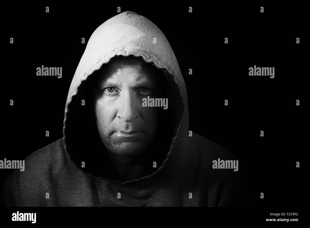 Dark and moody portrait of man in hoodie. Black and White image. - Stock Image