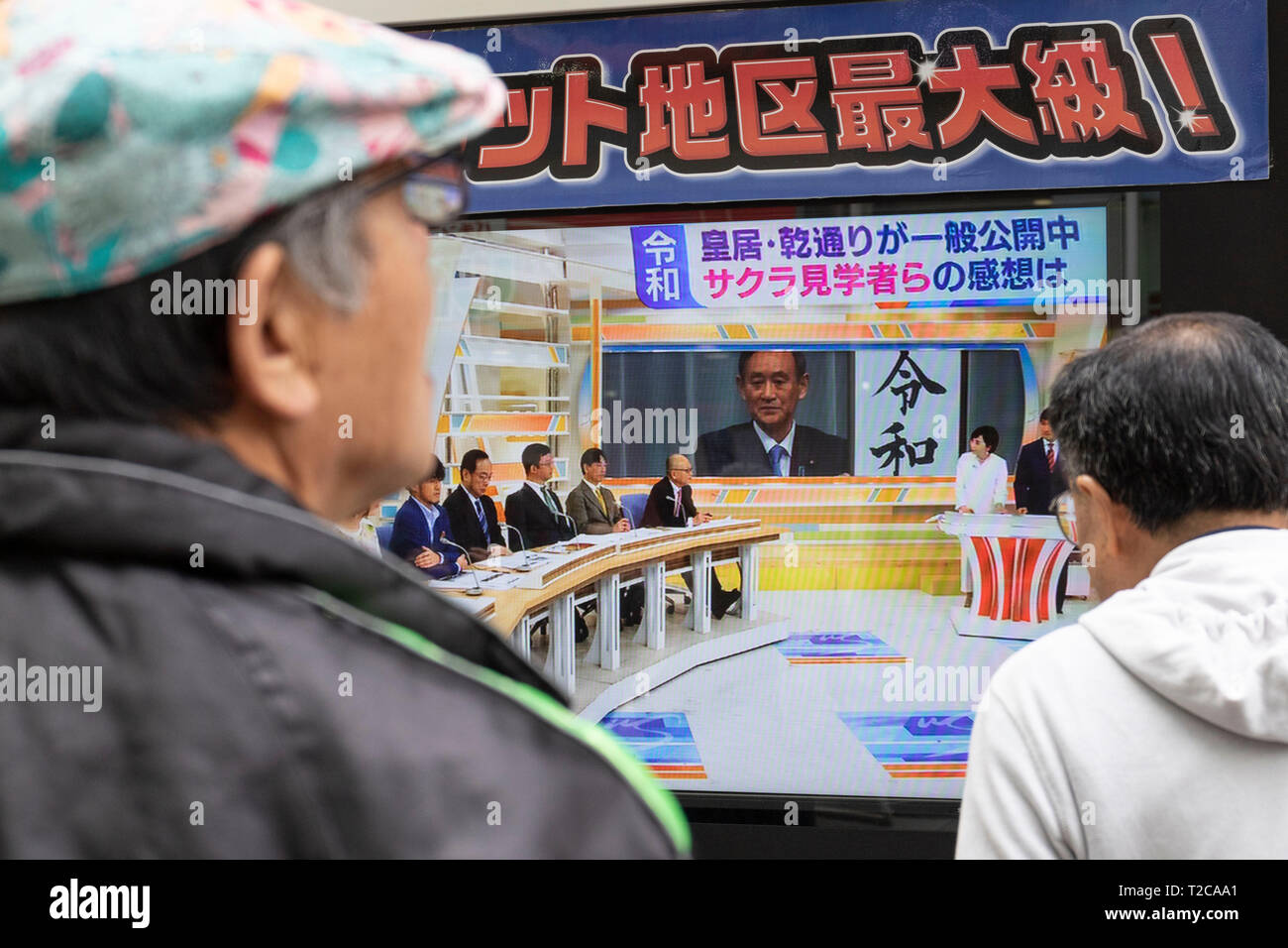 Tokyo, Japan. 1st Apr, 2019. Tokyo, Japan. 01st Apr, 2019. People look at a screen displaying the news of Japanese Chief Cabinet Secretary Yoshihide Suga showing the kanji ''Reiwa'' for the Imperial new era, in downtown Tokyo. The government announced ''Reiwa'' as new Imperial era name today, April 1st. The new era will start on May 1st when the Crown Prince Naruhito ascends the throne, after his father, Emperor Akihito, formally abdicates on April 30. Credit: Rodrigo Reyes Marin/AFLO/Alamy Live News - Stock Image