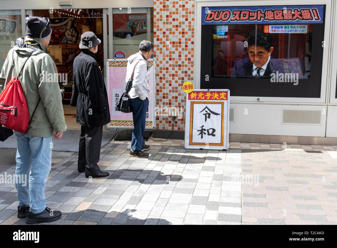 Tokyo, Japan. 1st Apr, 2019. Tokyo, Japan. 01st Apr, 2019. People look at a screen displaying the Japan's Prime Minister Shinzo Abe speaking about the new name ''Reiwa'' for the next Imperial era, in downtown Tokyo. Japanese Chief Cabinet Secretary Yoshihide Suga announced ''Reiwa'' as new Imperial era name today, April 1st. The new era will start on May 1st when the Crown Prince Naruhito ascends the throne, after his father, Emperor Akihito, formally abdicates on April 30. Credit: Rodrigo Reyes Marin/AFLO/Alamy Live News - Stock Image