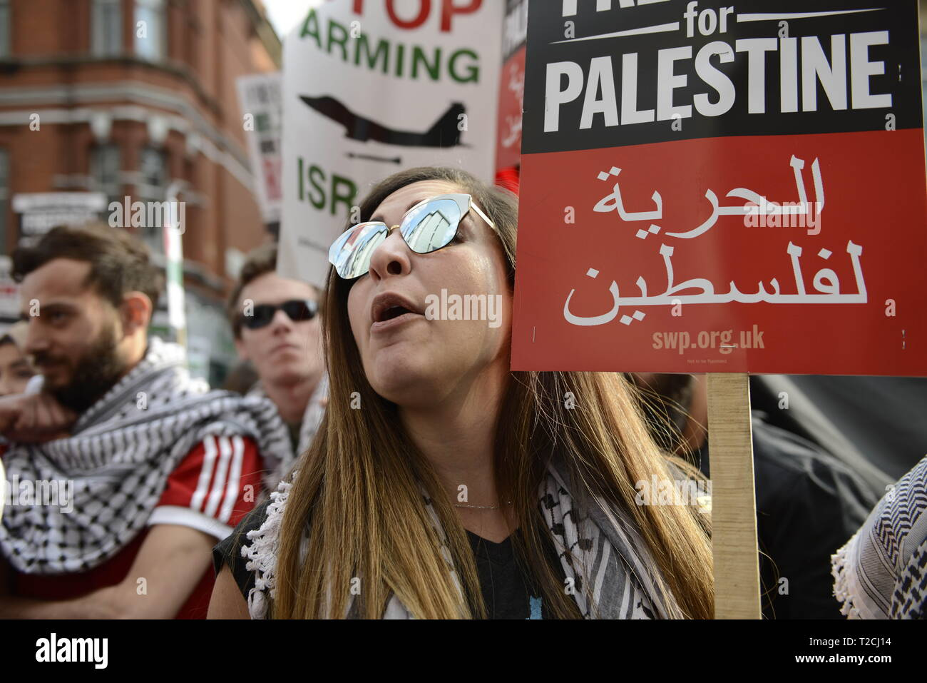London, Greater London, UK. 30th Mar, 2019. A protester is seen chanting slogans while holding a placard during the Exist, Resist, Return Rally for Palestine in London.People gather outside the Israeli embassy in London to demonstrate against the Israeli government, and to demand respect for Palestinians' fundamental rights to exist, resist and return. Palestinians are calling for global protests to support their right to come back to their villages. Rally was organized by Palestine Solidarity Campaign, Stop the War Coalition, Palestinian Forum in Britain, Friends of Al- Aqsa, - Stock Image