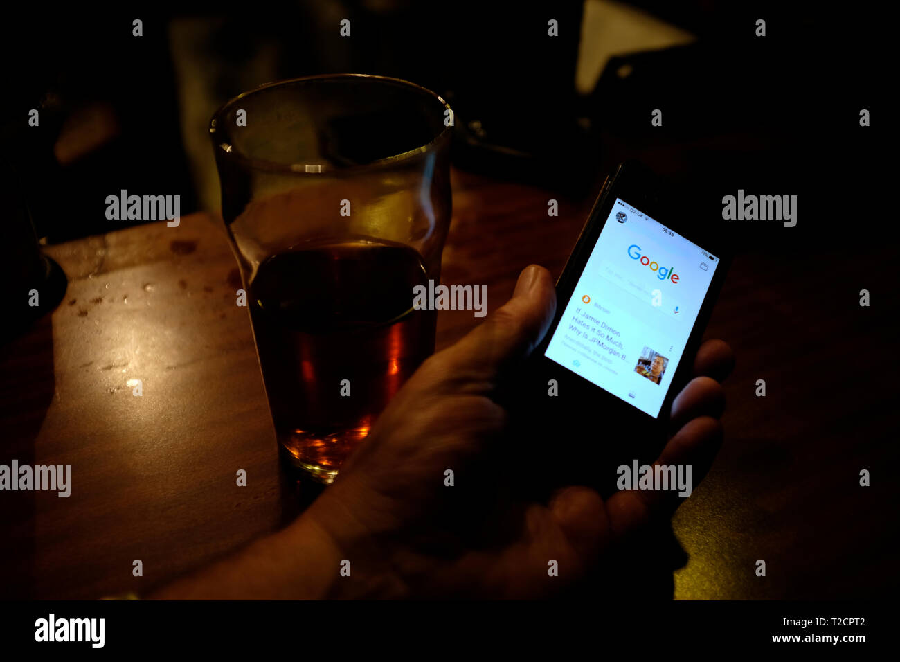 question,quiz,cheating,settling,pub,discussion,argument,using,Google,on,smartphone,iPhone, - Stock Image