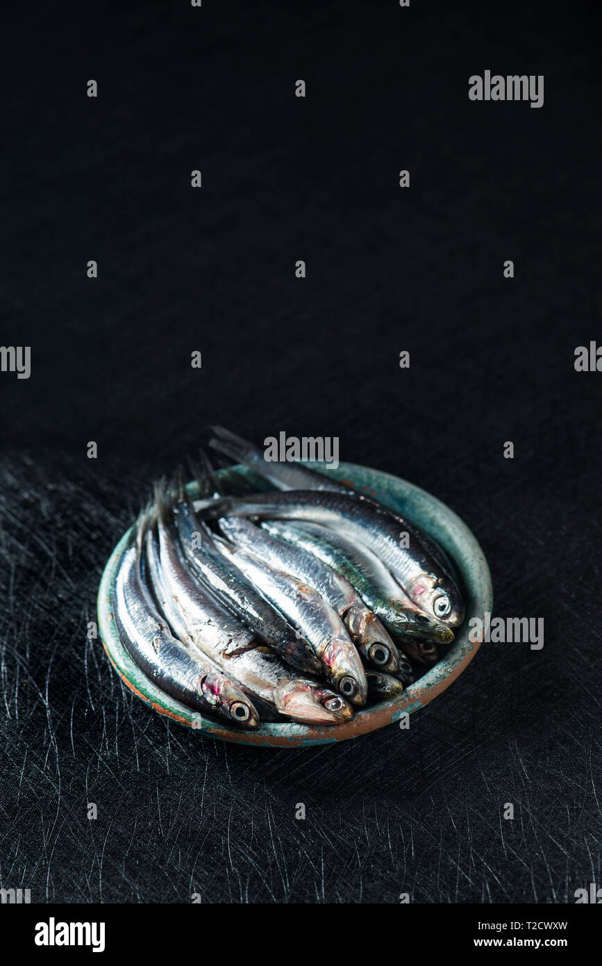 a rustic green earthenware plate with some raw spanish boquerones, anchovies typical in Spain, ready to be cooked, on a black textured surface, with s - Stock Image