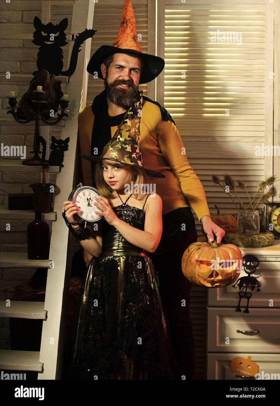 Girl and bearded man with tricky faces on carnival room background. Wizard and little witch in hats hold old clock and jack o lantern. Father and daug - Stock Image