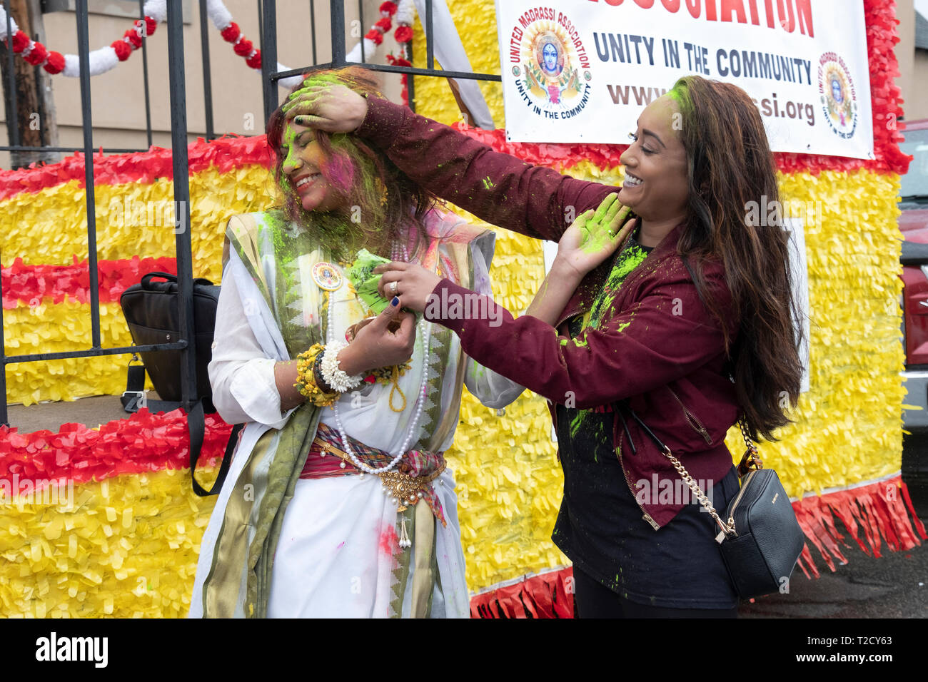 Two beautiful Hindu women throw powder at each other at the Holi Parade on Liberty Ave. in Richmond Hill, Queens, New York - Stock Image