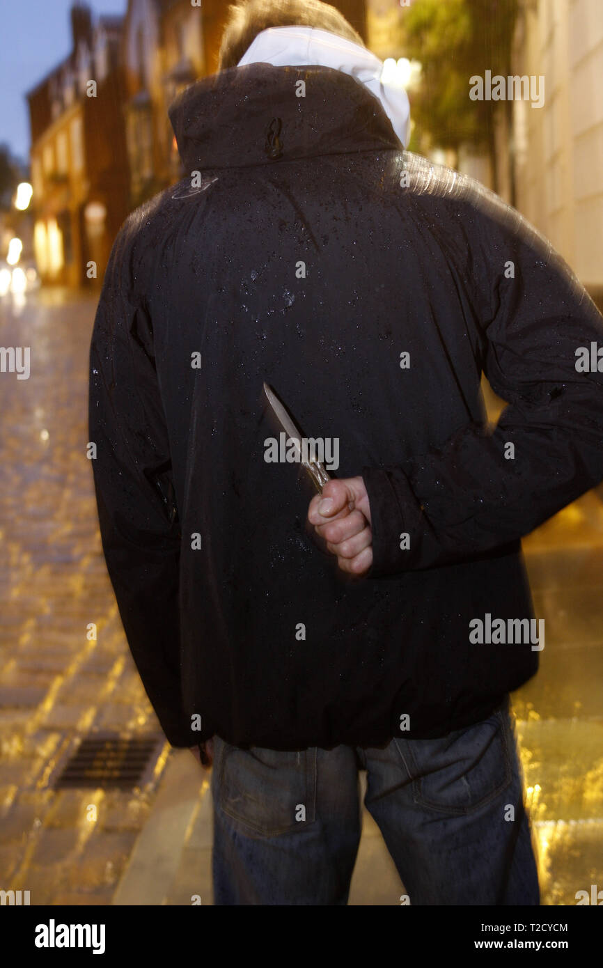 Knife crime. Hooded man brandishing a butterfly knife Stock Photo