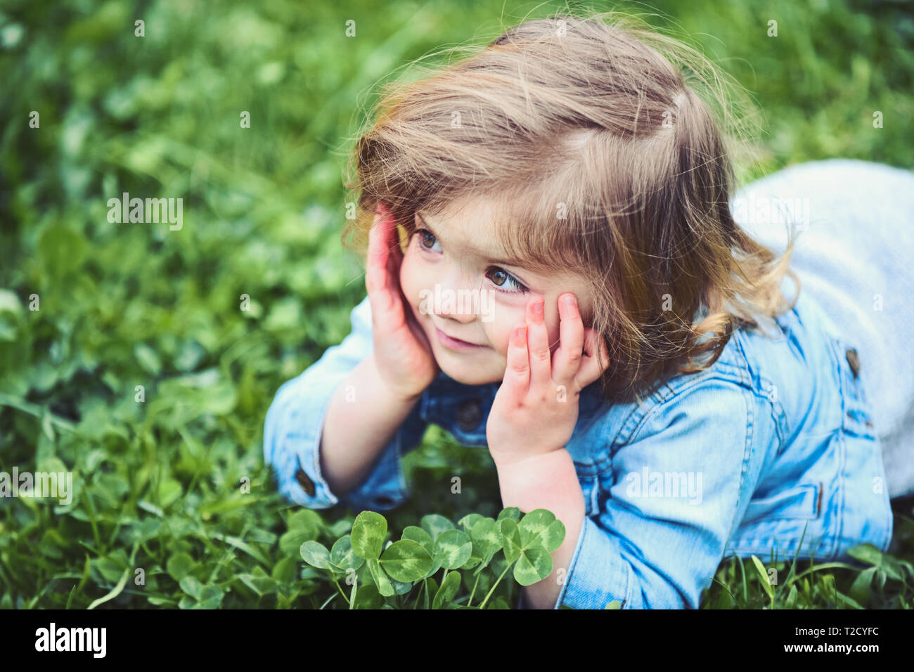 Cute child smile on green grass lawn. Little girl relax on spring or summer day outdoor. New life, youth, growth. Vitality, wellness, health, lifestyl - Stock Image
