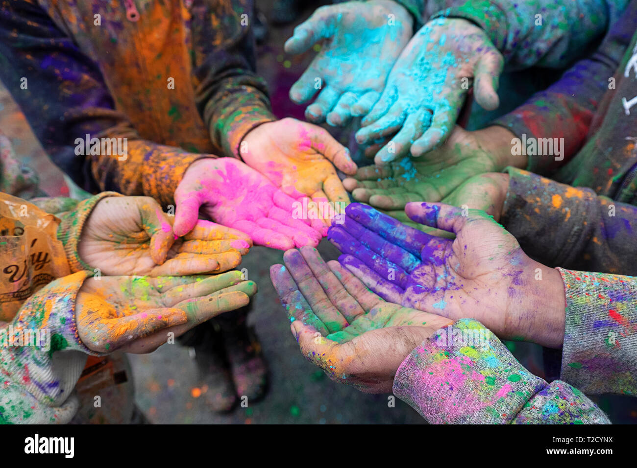 Children's hands at the Holi Parade on Liberty Ave in Richmond Hill, Queens, New York where it's customary to throw & smear colored powder. - Stock Image