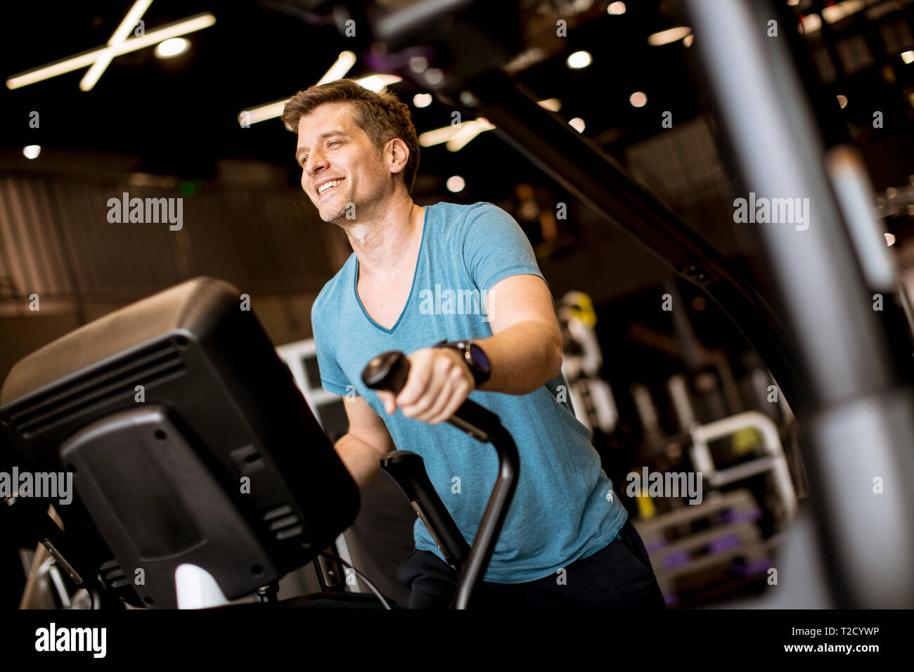Young man doing exercise on elliptical cross trainer in sport fitness gym club - Stock Image