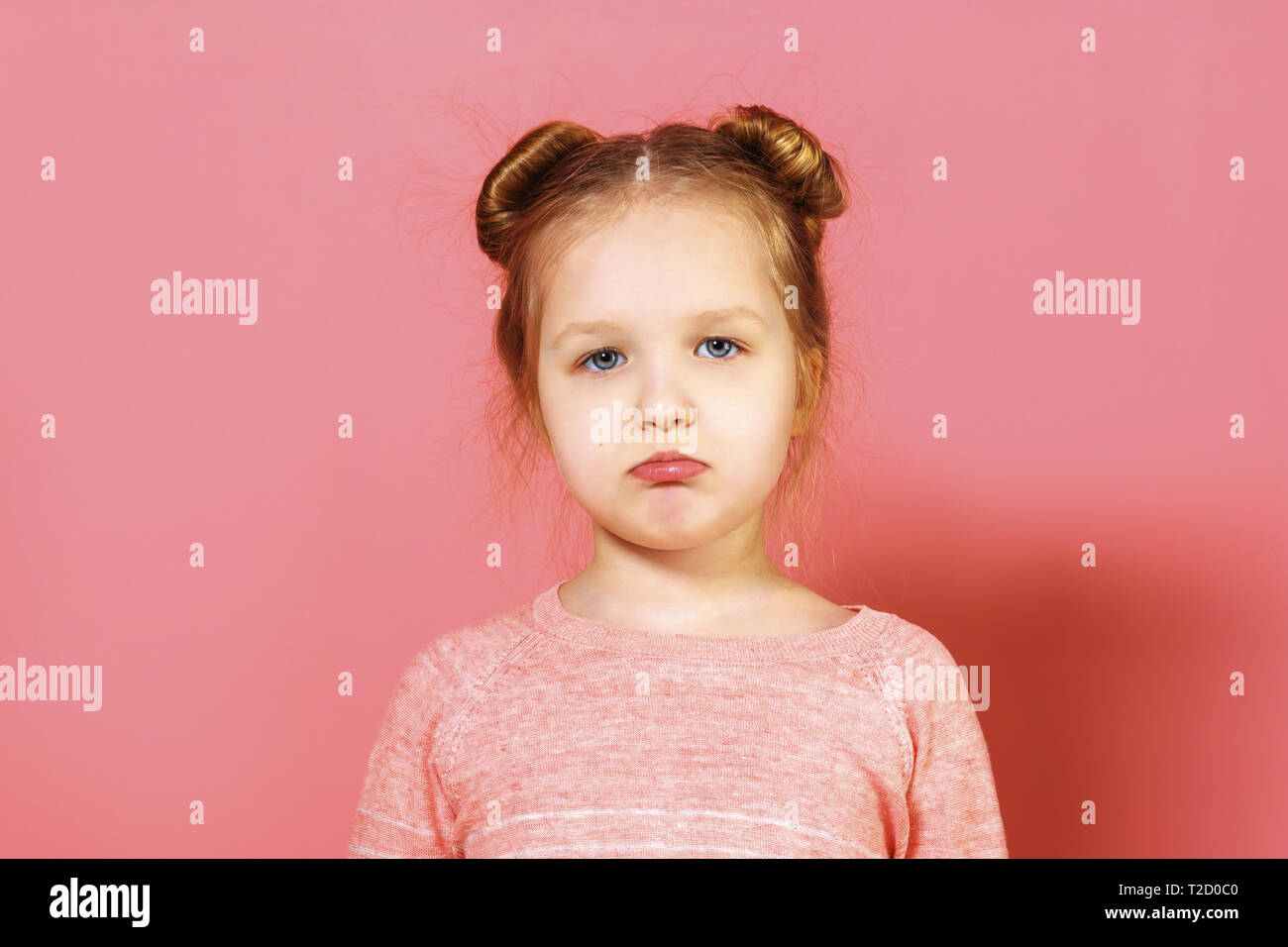 Closeup portrait of upset little girl with wisps of hair over pink background. The child pouted his lips. - Stock Image