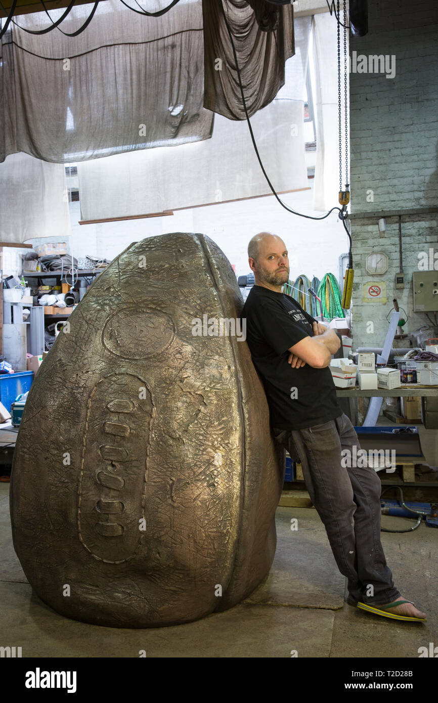 Sculptor Gavin Turk with his rugby ball sculpture 'Birth of the Egg Ball' at its bronze forged stage of creation for Rugby School, birthplace of the s - Stock Image