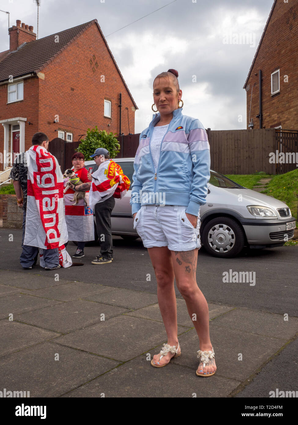 A woman in white shorts and Ellesse tracksuit top. - Stock Image