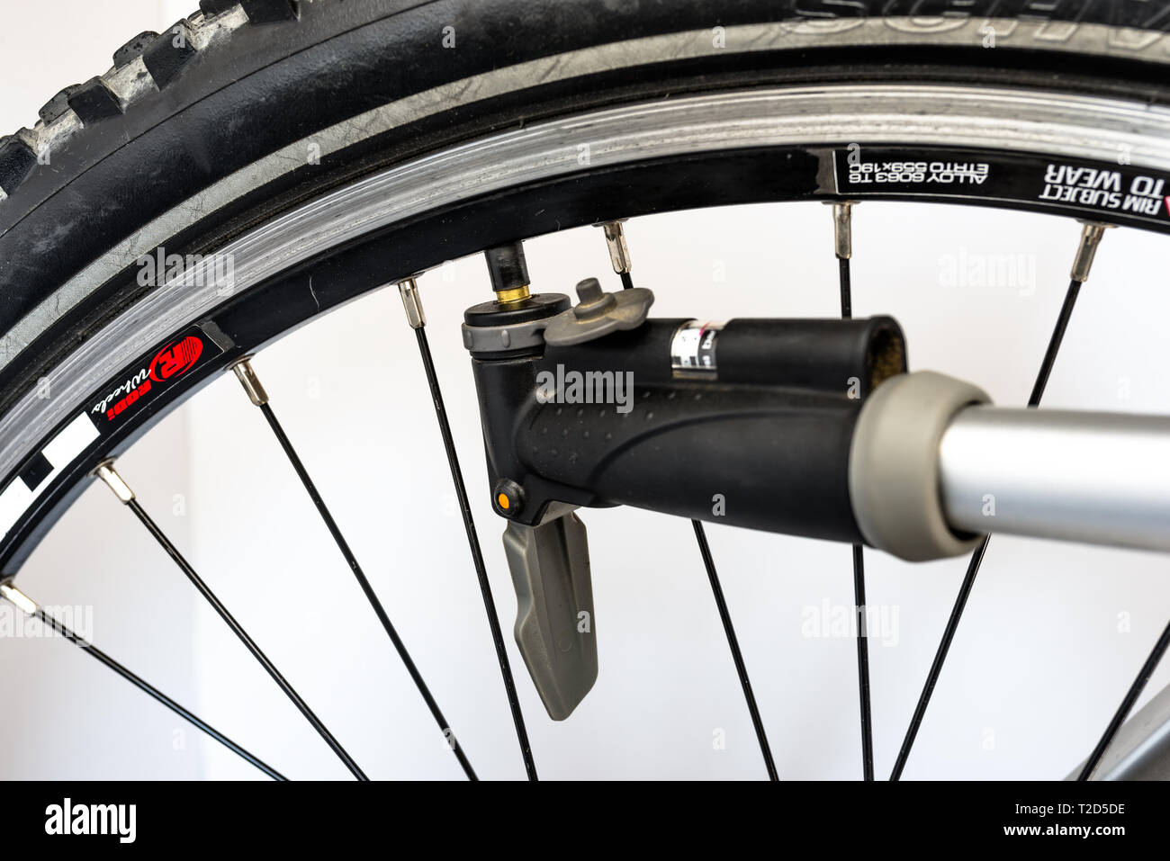 Bonn, Germany - March 29, 2019. Pumping the bicycle wheel using a hand pump with air pressure indicator in units of bar / psi. - Stock Image