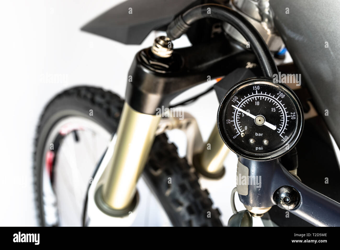 Pumping of the front, bicycle oil-air shock absorber using a specialized hand pump, visible pressure indicator in units of bar / psi. - Stock Image