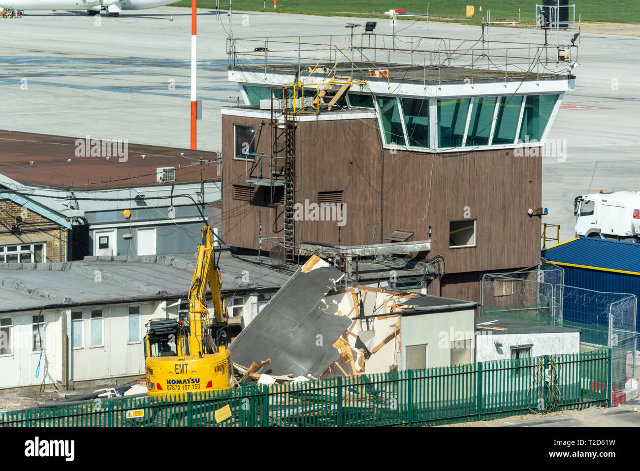 Old building being demolished close to the old disused air traffic control tower at London Southend Airport, Essex, UK. Redevelopment of airport - Stock Image