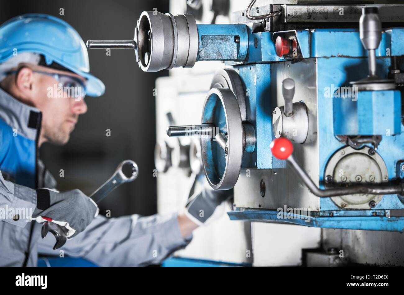 Caucasian Lathe Machine Technician with Wrench Trying To Adjust Machinery Elements. Metalworking Industry Theme. - Stock Image