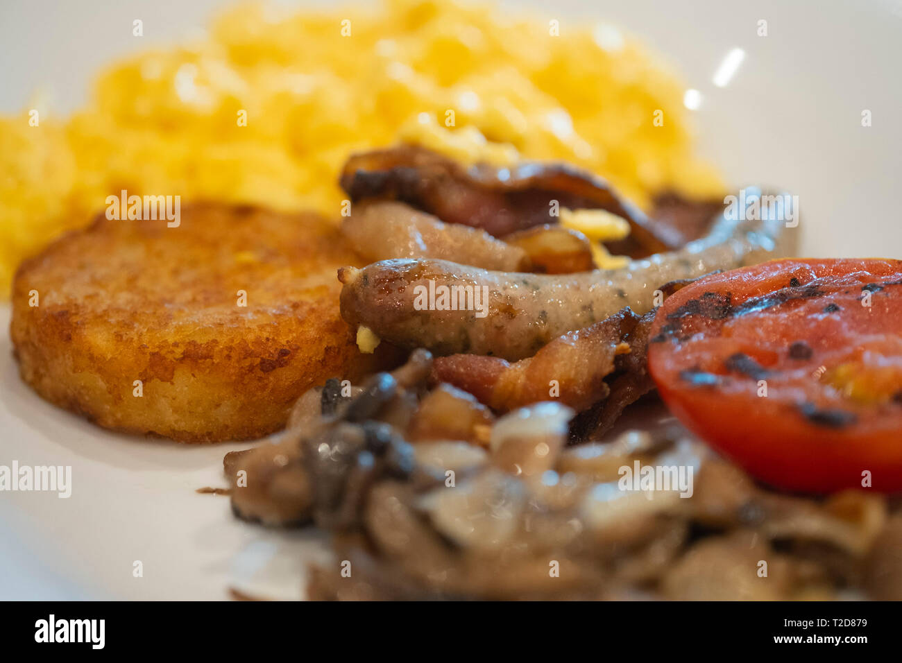 Breakfast plate with scrambled eggs, sausages, tomatoes and hash browns Stock Photo